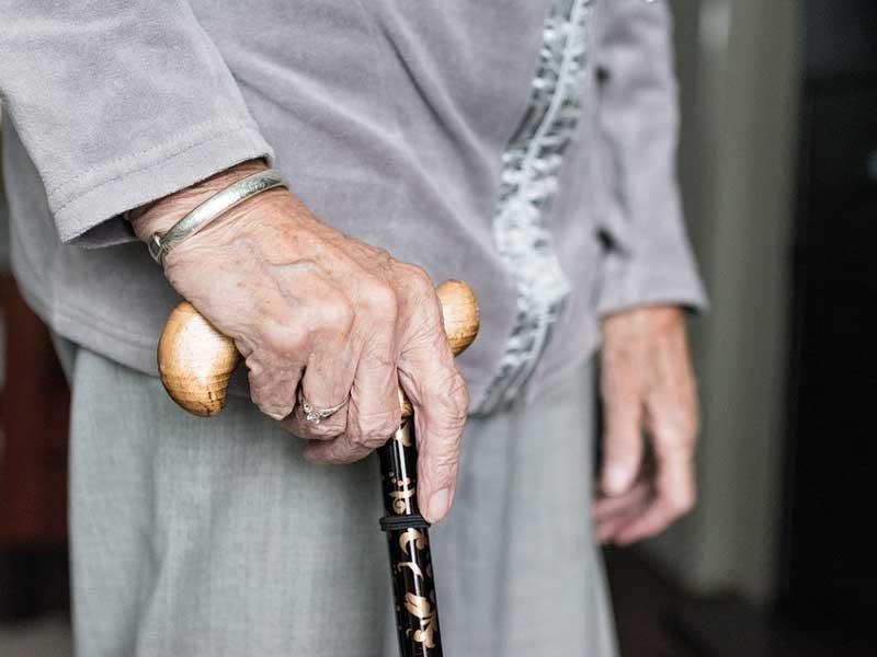 ältere Person mit Gehstock